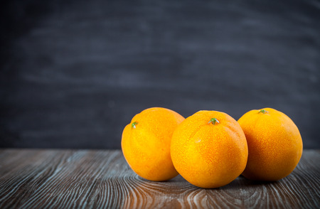 ingradient: Oranges on wooden table dark background, copy space