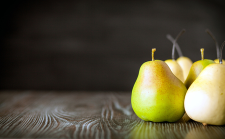 ingradient: Green pears on wooden board dark background, copy space