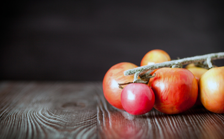 ingradient: Tomatoes on branch. Wooden board dark background, copy space