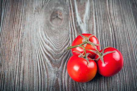 ingradient: Tomatoes on wooden table dark background, copy space
