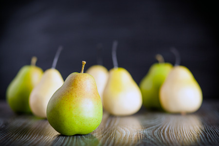 ingradient: Green pears on wooden table dark background, front view