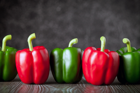 ingradient: Red and green bell pepper on wooden board dark background, copy space Stock Photo