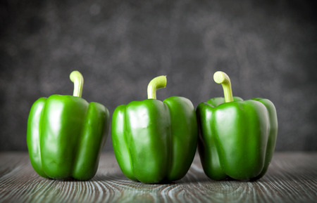 ingradient: Green bell pepper on wooden board dark background, front view Stock Photo