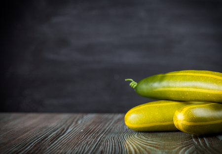 ingradient: Cucumber on wooden table dark background, copy space