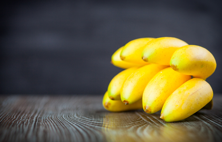 ingradient: Bunch of bananas on wooden table dark background, copy space Stock Photo