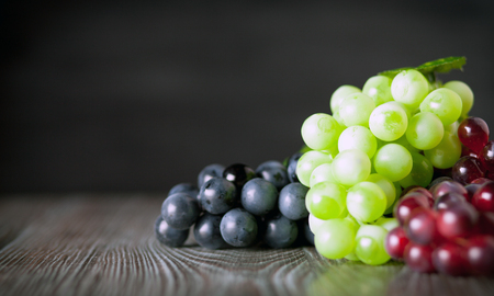 ingradient: Colorful grape on wooden board dark background, copy space Stock Photo