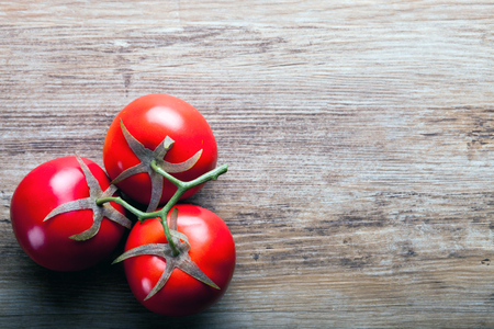 ingradient: Fresh ripe tomatoes on wooden board background with copy space