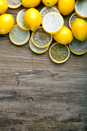 ingradient: Fresh ripe lemons on wooden board, background with copy space