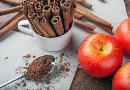 ingradient: Cinnamon sticks, powder and ripe apples on rustic wooden board, top view