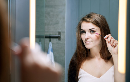 Young woman applying mascara on long eyelashes in front of a bathroom mirror Stock Photo