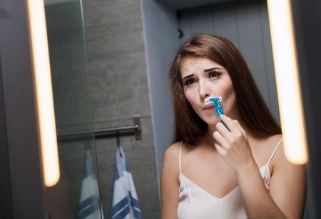 Young woman shaving mustache in front of a bathroom mirror Foto de archivo
