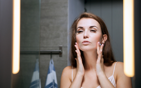 antiaging: Young woman checking wrinkles on face in front of a bathroom mirror Stock Photo