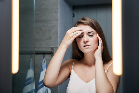 doctor burnout: Young woman with headache in front of a bathroom mirror Stock Photo