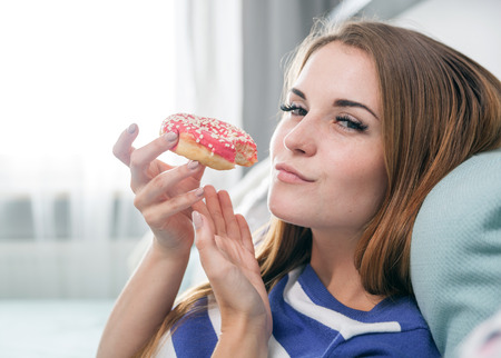 Woman at home eating fresh red donut and relaxing