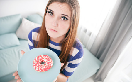 Woman on diet with unhealthy donut thinking about eating it Stock Photo