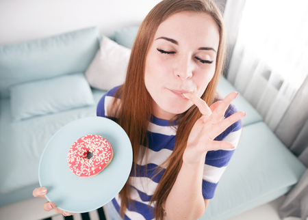 finger licking: Woman at home eating red donut and licking her finger Stock Photo