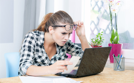 calculating: Desperate and worried young woman calculating bills in home office Stock Photo
