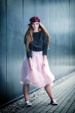 Trendy beautiful long haired girl posing on street, hip hop fashion Stock Photo