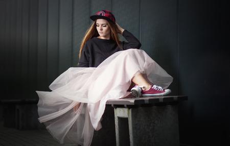 rnb: Trendy beautiful long haired girl posing on street, hip hop fashion Stock Photo