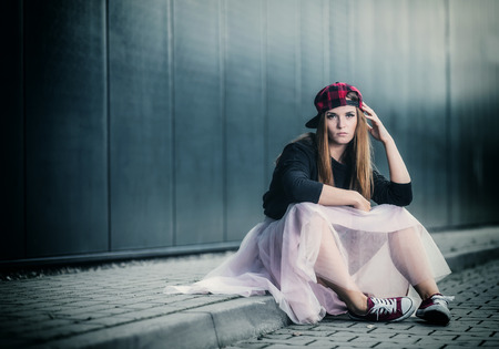 Trendy beautiful long haired girl posing on street, hip hop fashion Stock Photo