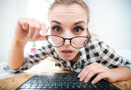 Überraschte Frau mit Laptop im Büro zu Hause im Internet Surfen, Blick vom Bildschirm