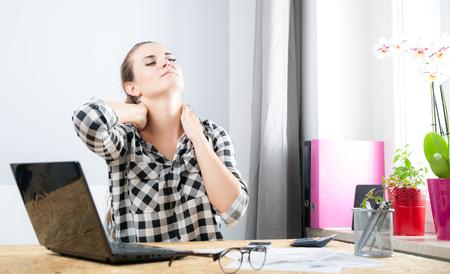 Müde junge Frau mit Nackenschmerzen während der Arbeit im Büro zu Hause