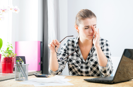 Tired young woman with eye pain during working in home office using laptop