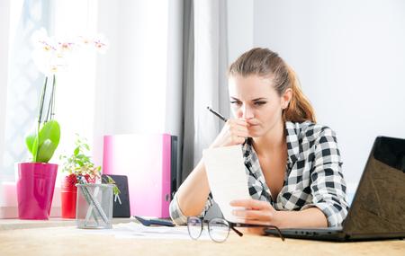 pagando: La mujer joven el cálculo y el pago de facturas en Ministerio del Interior