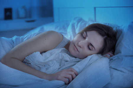 Woman peacefully sleeping in bed at night Stock Photo - 69082986