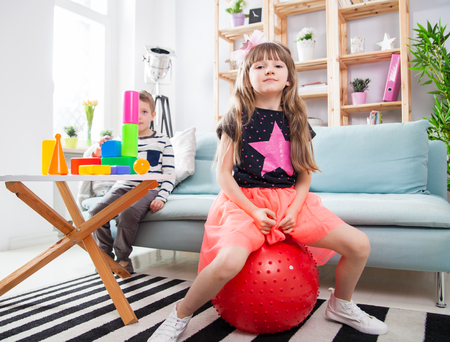 Siblings playing with colorful blocks and fitness ball at home