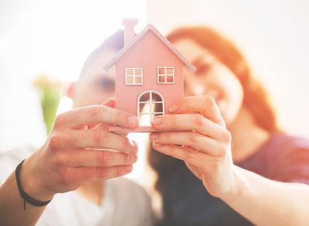 Jonge liefdevolle paar met een klein houten huis nieuw huis concept Stockfoto - 75087888