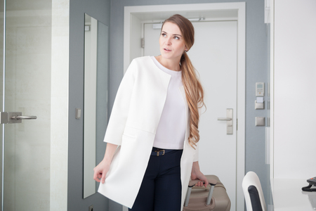 Young delighted woman pulling suitcase in modern hotel room
