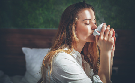 Pretty young woman in modern apartment drinking coffee after wake up Stock Photo