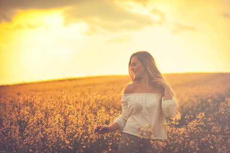 canola: Happy smiling woman in yellow rapeseed field at sunset Stock Photo
