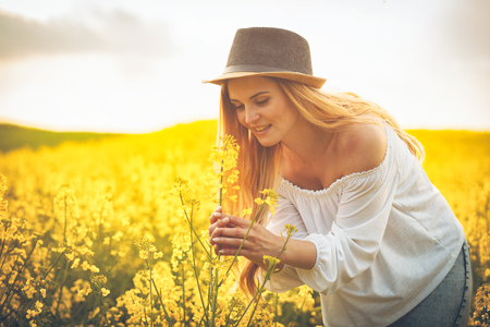 Happy smiling woman with hat in yellow rapeseed field at sunset