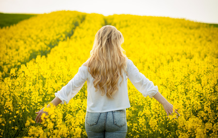Woman with long hair back view, yellow rapeseed field