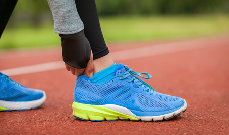 Athletic woman on running track touching hurt leg with ankle injury during workout