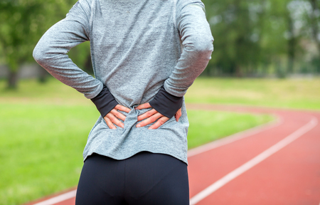 Athletic woman on running track touching hurt back with painful injury during workout Stock Photo