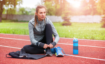 Athletic woman on running track tying shoe laces, sport fitness accessories