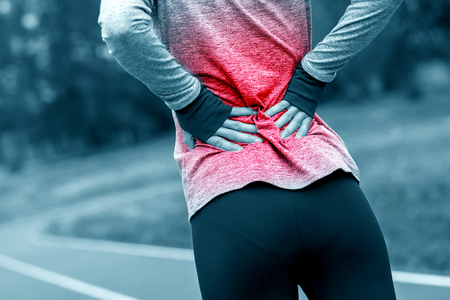 Athletic woman on running track touching hurt back with painful injury during workout Stockfoto