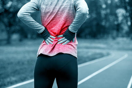 Athletic woman on running track touching hurt back with painful injury during workout Standard-Bild