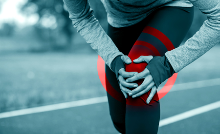 Athletic woman on running track touching hurt leg with knee injury during workout