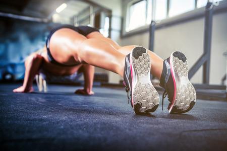 cross: Sport wear shoes closeup, fitness woman doing push ups training at gym Stock Photo
