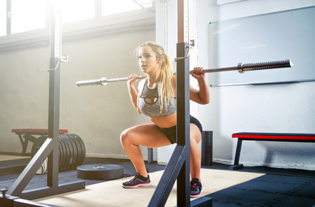Woman doing squats with barbell at the crossfit gym
