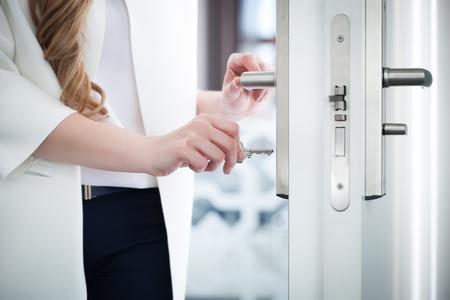 Locking or unlocking modern door with key in hand 版權商用圖片