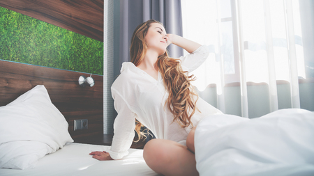 domicile: Pretty young woman on bed in modern apartment smiling and stretching after wake up