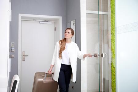 モダンなホテルの部屋でスーツケースを引いて若い女性