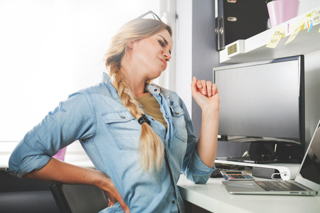 Woman in home office suffering from back pain sitting at computer desk
