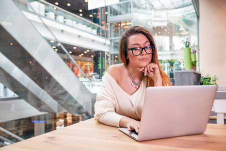Young business woman with laptop working at open space office in modern interior