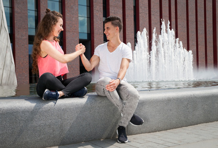 Young couple sitting in town outdoor and giving high five, success concept